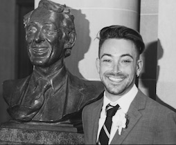 a man standing next to a bust of harvey milk