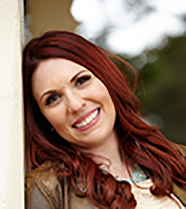 outside. a woman with long red hair smiles at camera