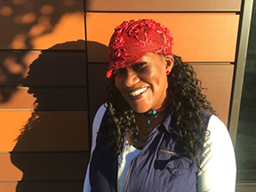 a woman, stands outside and is smiling. she is wearing a red hat and a white shirt